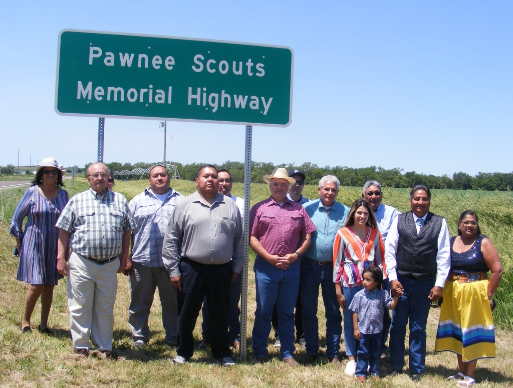 Group photo of people gathered beneath Pawnee Scouts Memorial Highway sign.